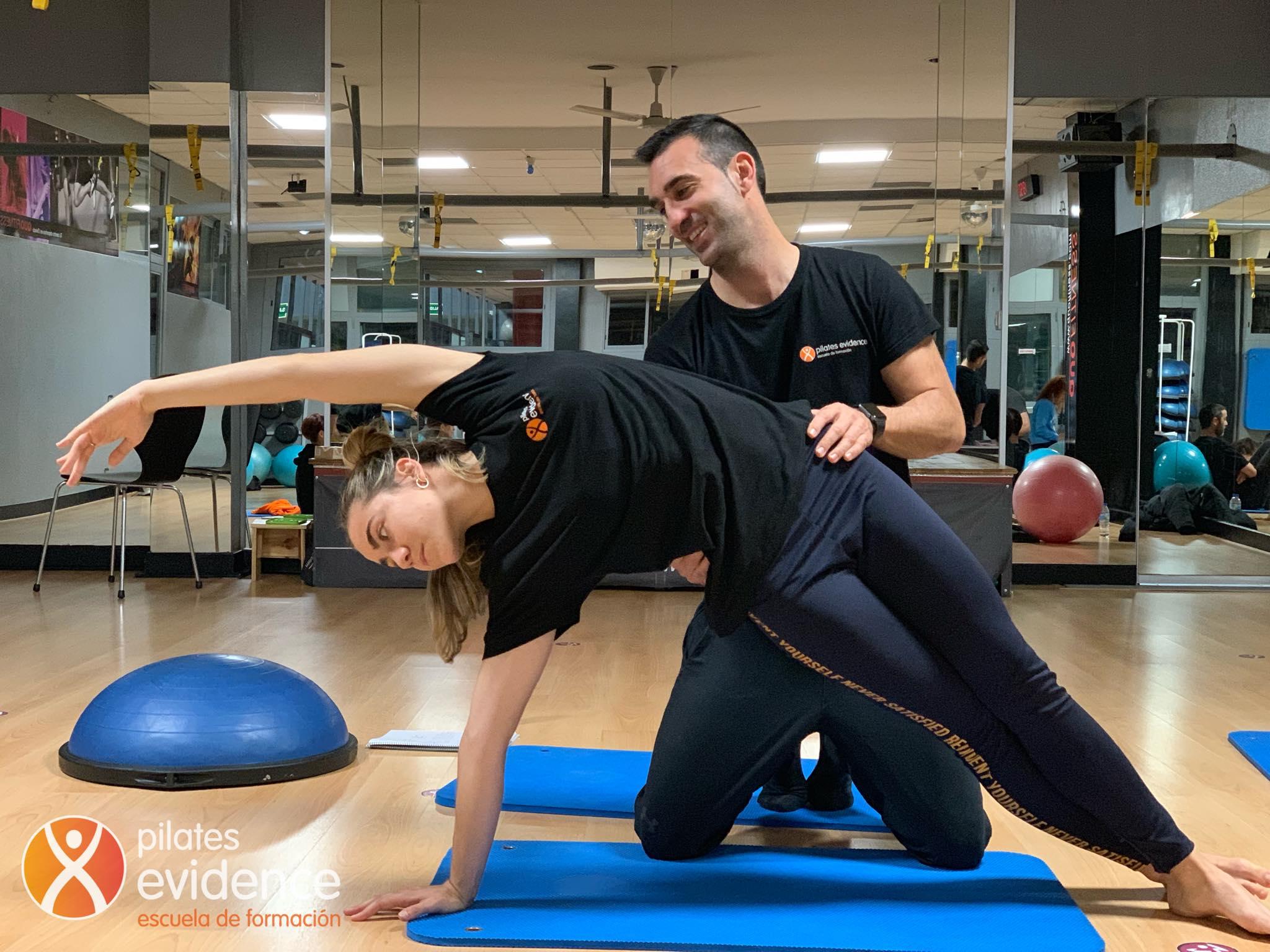 Un instructor de Pilates ayudando a que una alumna domine una nueva técnica de pilates