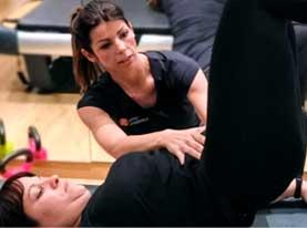 Una instructora ayudando a una alumna a mejorar su postura durante el ejercicio