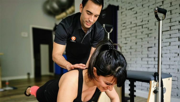 instructor de pilates corrigiendo un ejercicio a una alumna